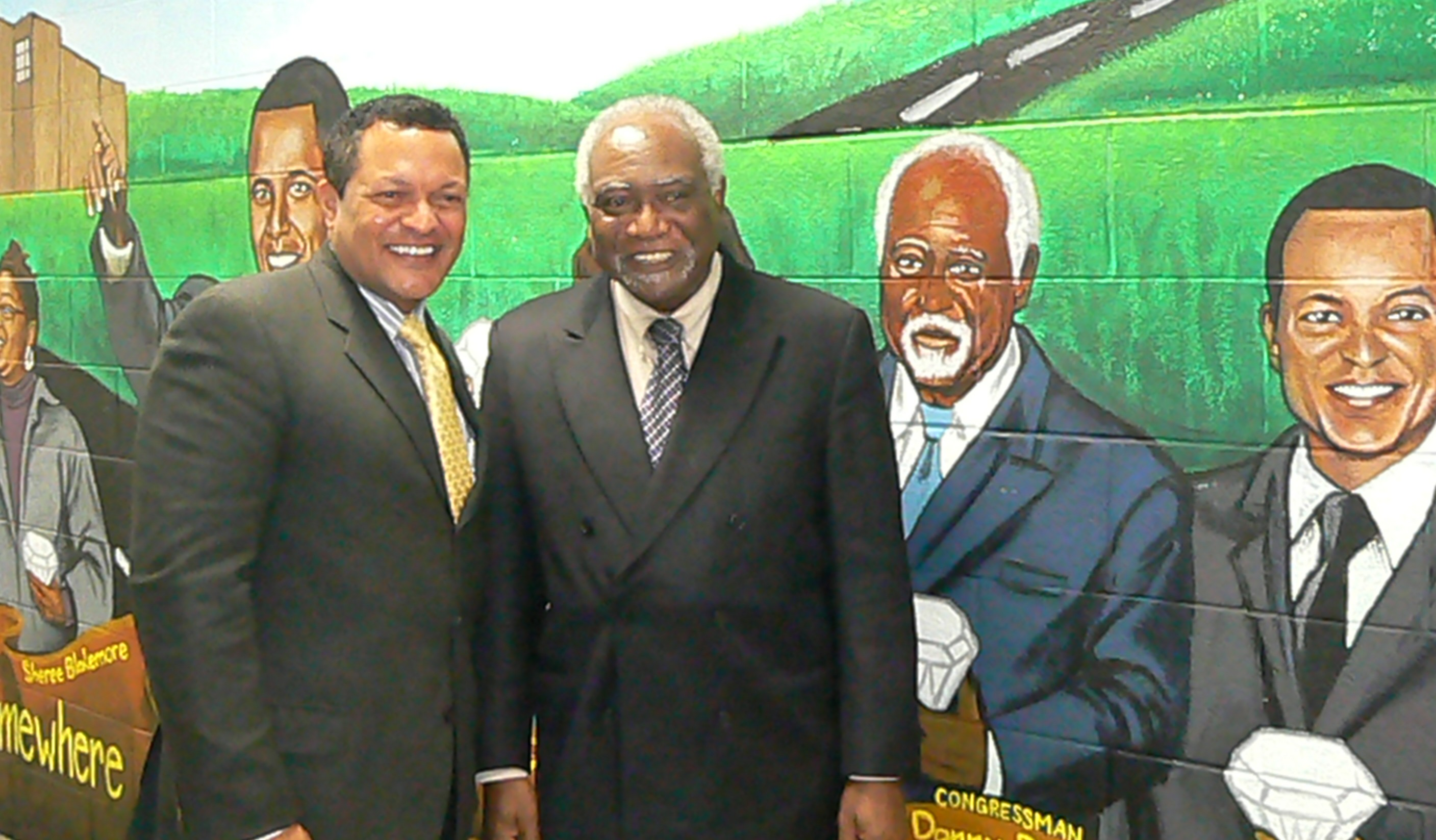 Cong. Danny Davis and Kenneth Morris stand beside their images painted in a mural at Frederick Douglass High School.